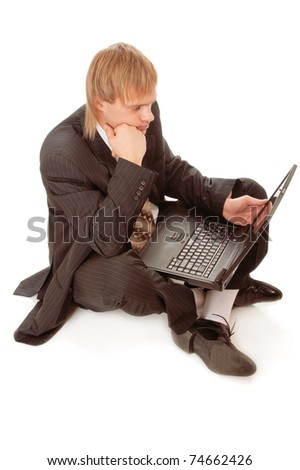 Young businessman sitting on floor with laptop isolated on white background - stock photo