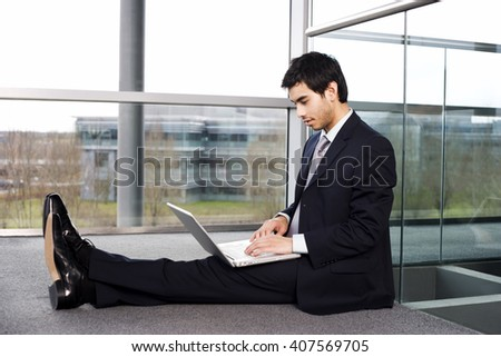 Young businessman sitting on office floor, typing on a laptop