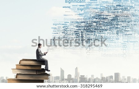 Young businessman sitting on pile of books with mobile phone in hands - stock photo