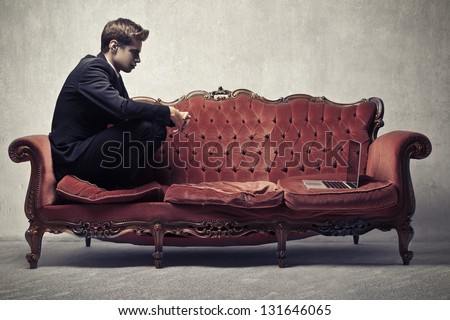 young businessman sitting on red sofa with laptop - stock photo