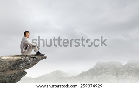 Young businessman sitting on rock edge and relaxing