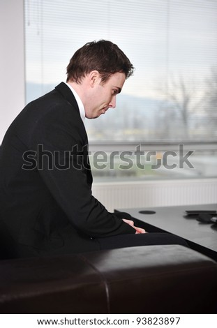 Young businessman sitting on sofa at office lobby