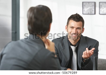 Young businessman sitting on sofa at office talking to businesswoman, smiling. - stock photo