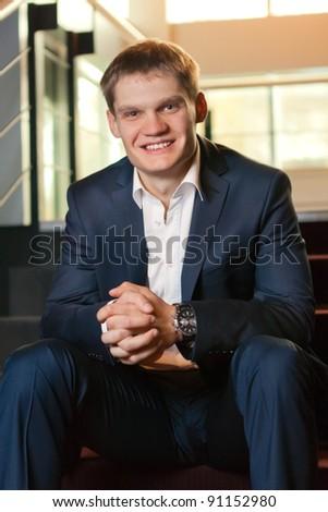 Young businessman sitting on stairs looking at camera - stock photo