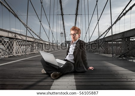 Young businessman sitting on the Brooklyn Bridge and using a laptop