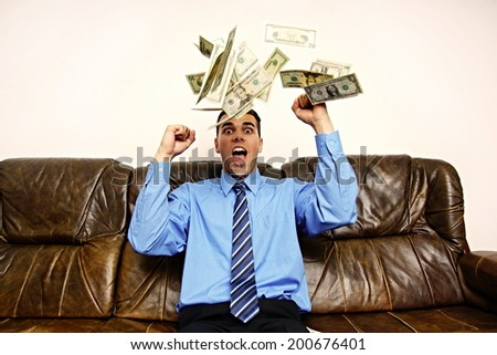 Young businessman sitting on the couch is surprised by the rain of money - stock photo