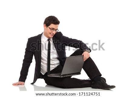 Young businessman sitting on the floor and using laptop. Full length studio shot isolated on white.