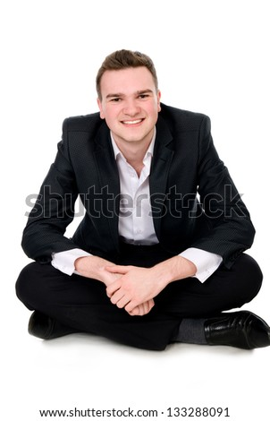Young businessman sitting on the floor, isolated on white background - stock photo