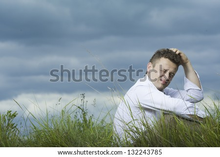 Young businessman sitting on the meadow. Thinking about something and scratching his head. Sky and meadow in the background. - stock photo