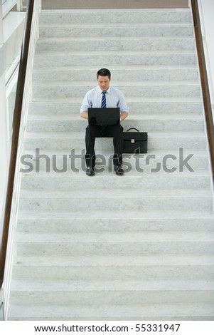 Young businessman sitting on the steps of stairs in front of a laptop computer