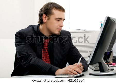 Young businessman sitting on the workplace. - stock photo