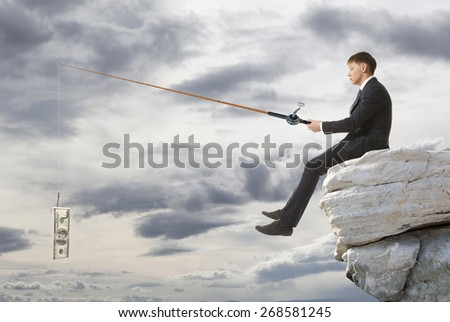 Young businessman sitting on top of rock and fishing - stock photo