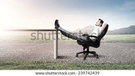 Young businessman sitting relaxed in chair with legs on table - stock photo