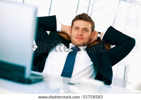 Young businessman sitting relaxed in his chair with hands under his head.