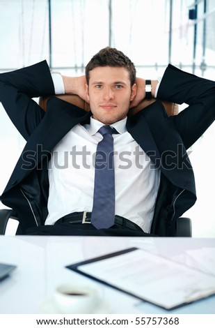 Young businessman sitting with his hands under his head looking at you.
