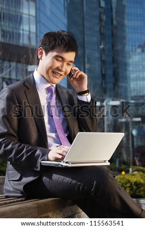 Young businessman sitting with laptop. Outdoor. - stock photo
