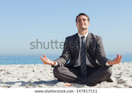 Young businessman sitting with legs crossed relaxing on the beach - stock photo