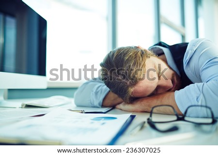 Young businessman sleeping by his desk in office - stock photo