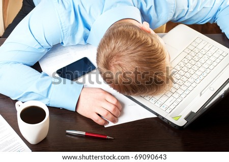 Young businessman sleeping on his table - stock photo