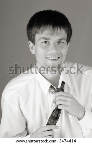 young businessman smiles and corrects for  tie - stock photo