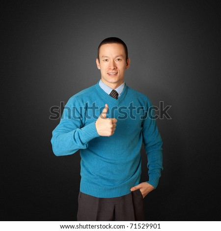 young businessman smiles on camera and shows well done - stock photo