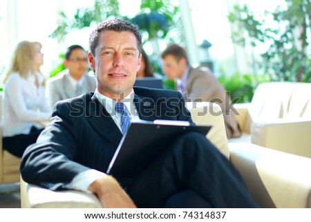Young businessman smiles towards the camera while his colleagues meet in the backgroun - stock photo
