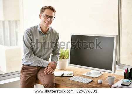 Young businessman smiling and sitting on the edge of his wooden desk in a bright office space - stock photo