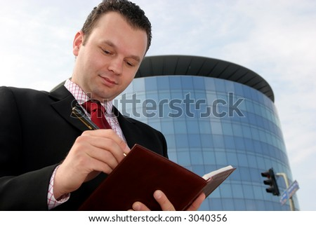 Young businessman smiling and taking notes in front of a corporate building - stock photo