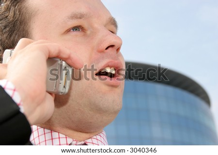 Young businessman smiling and talking on a cell phone in front of a corporate building - stock photo