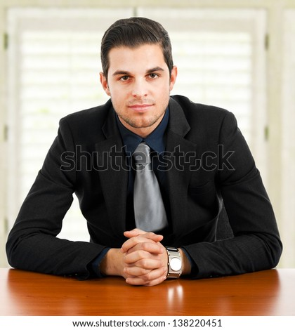 Young businessman smiling at his desk in a modern office  - stock photo