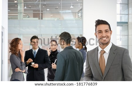 Young businessman smiling at office lobby, group of young businesspeople standing at background.