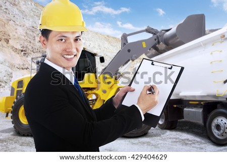 Young businessman smiling at the camera while writes on a clipboard with mining vehicle at mining site - stock photo