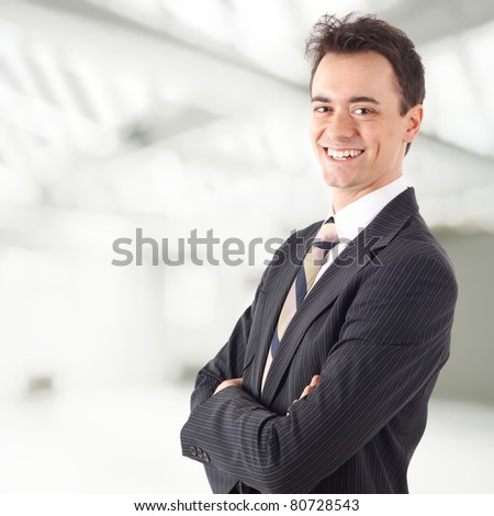 Young businessman smiling. Blurred bright background. - stock photo