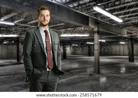 Young businessman smiling inside a construction site - stock photo