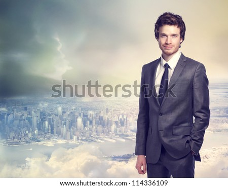 Young businessman smiling on top of the city - stock photo