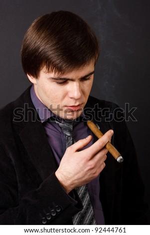 young businessman smoking a cigar - stock photo