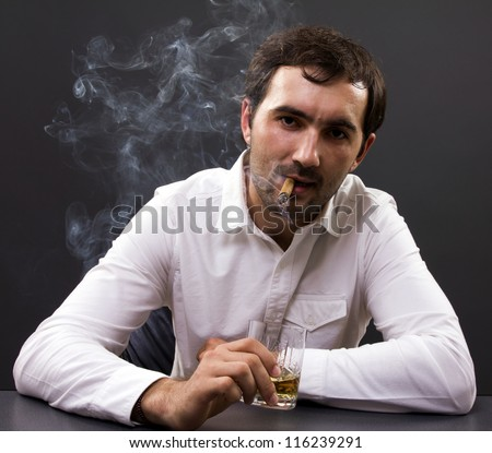Young businessman smoking a cigar enjoying a glass of whiskey in his office - stock photo