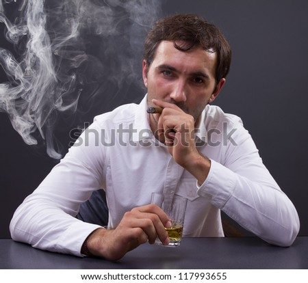 Young businessman smoking a cigar enjoying a glass of whiskey in his office, portrait of a young man - stock photo