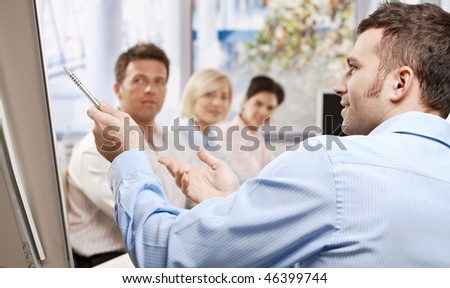 Young businessman speaking on business presentation in meeting room, pointing with pen, explaining, side view. - stock photo