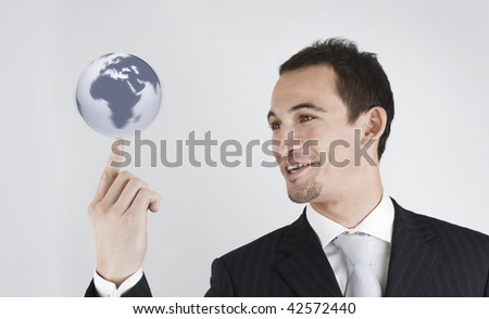 young businessman spinning (holding) the world (globe) in his finger - stock photo