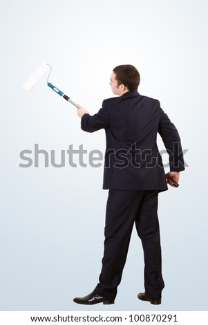 Young businessman standing against blank wall with brush - stock photo