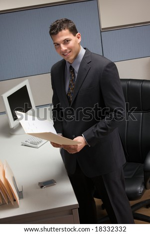 Young businessman standing at desk in cubicle holding file folder - stock photo