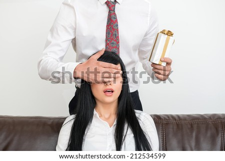 Young businessman standing behind and holding present for pretty and surprised woman sitting on sofa  and closing with his hand  her eyes in office interior - stock photo