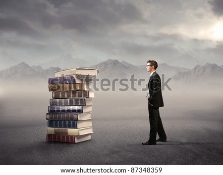 Young businessman standing beside a stack of books