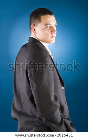 young businessman standing (blue background) - stock photo