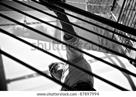 Young businessman standing in bright office balcony. Black-white photo. - stock photo
