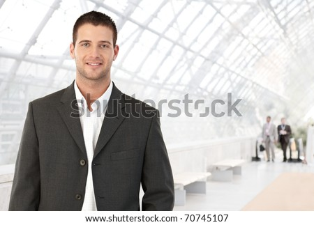 Young businessman standing in bright office lobby smiling at camera. - stock photo