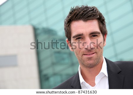 Young businessman standing in front of buildings - stock photo