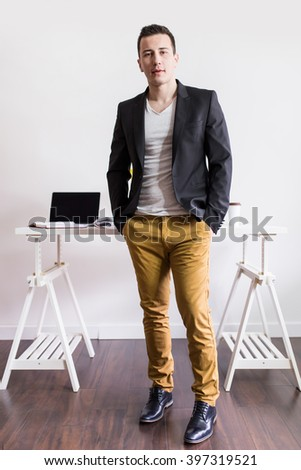 Young businessman standing in front of his desk. Depth of field, selective focus  - stock photo