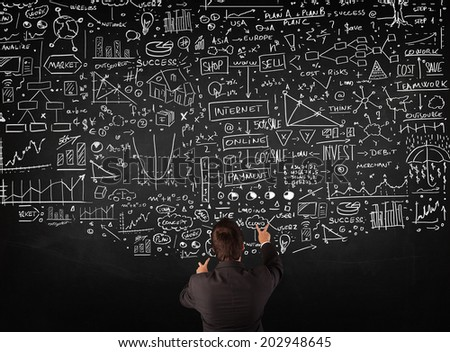 Young businessman standing in front of sketched charts and signs on a blackboard - stock photo